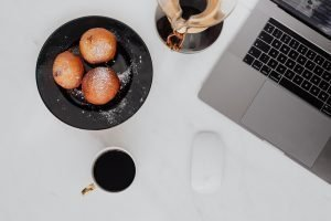 kaboompics Marble desk with laptop homemade Polish doughnuts and coffee