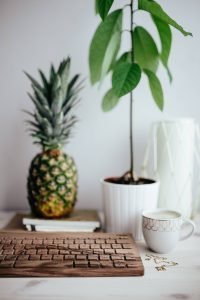 kaboompics Wooden keyboard cup of coffee pineapple and golden jewellery